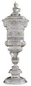 Willkomm - 19. Jahrh. - Silber (handgetrieben) mit Deckel (darauf Bekrönung) - innen vergoldet. Ziseliert mit Wappen und Jagdszenen (sogenannter Hubertus-Pokal) Augsburg